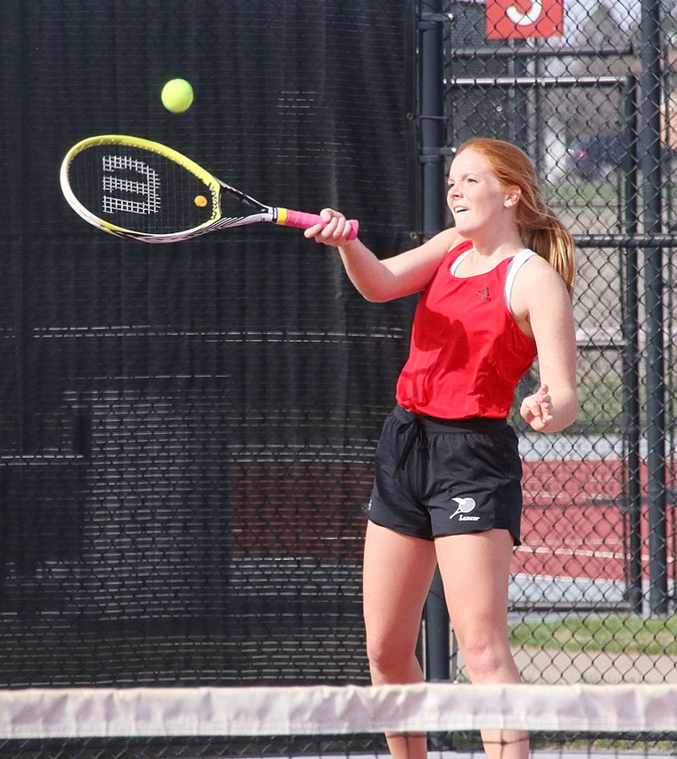 Lancer junior Lauren Youngers squints into the sun as she returns this volley in her No. 5 singles match against Muscatine.