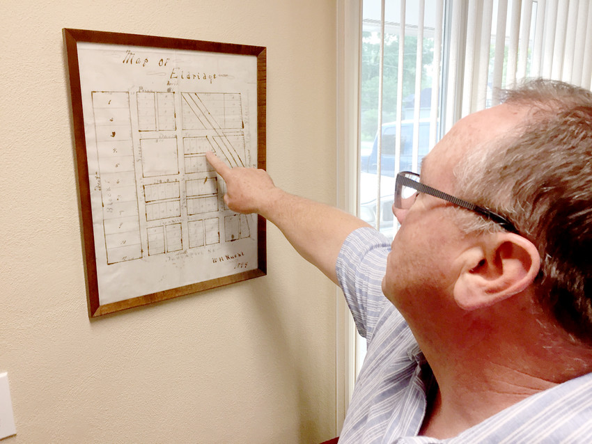 Robert Guy uses an 1894 map in Eldridge City Hall to show where the old Railroad Street clips the corner of his property at 420 N. Second St.