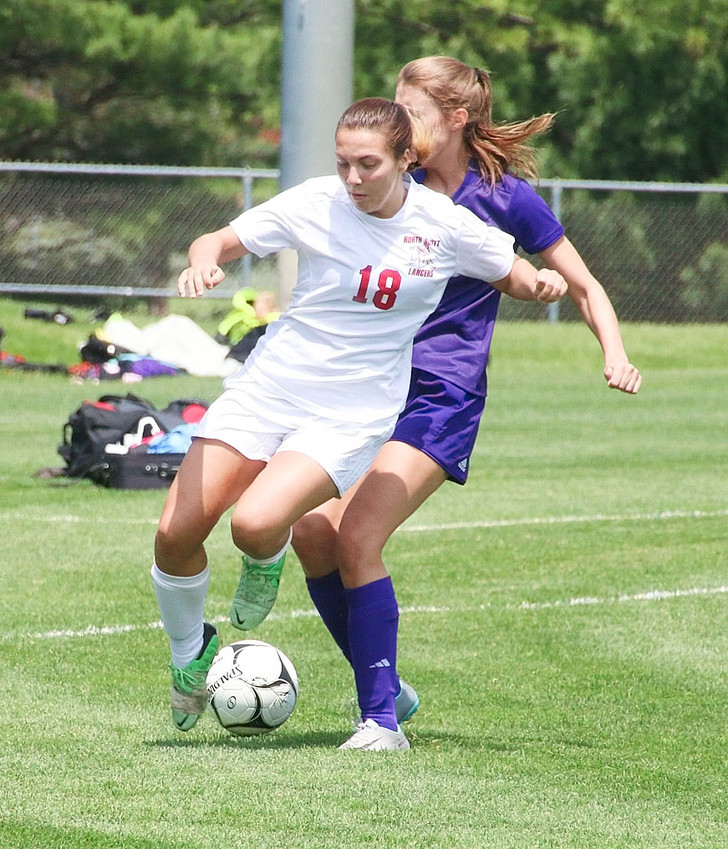 Lancer senior Adelyn Carmody turns the corner and bulldozes her way past a Central DeWitt defender on Saturday.