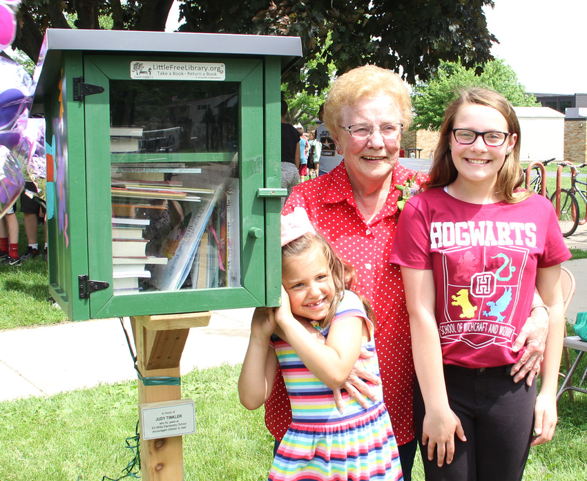 Retired school librarian Judy Tinkler poses with students Liza Clark, left, and Dakota Lindsey, right, who decorated the library.
