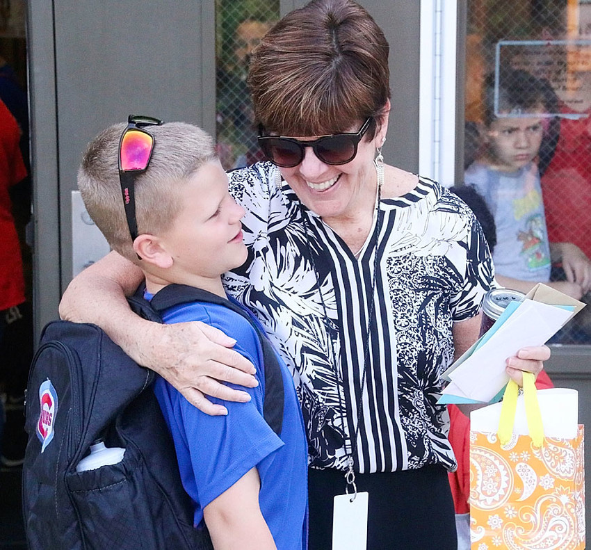 Retiring Alan Shepard principal Sherri Marceau shares a hug with second-grader Drake Huffman as she greets students on the last day of school.