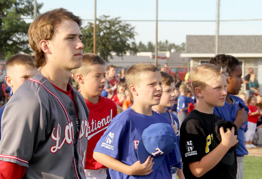 Lancer shortstop Cayle Webster stands with Little Leaguers for the national anthem.