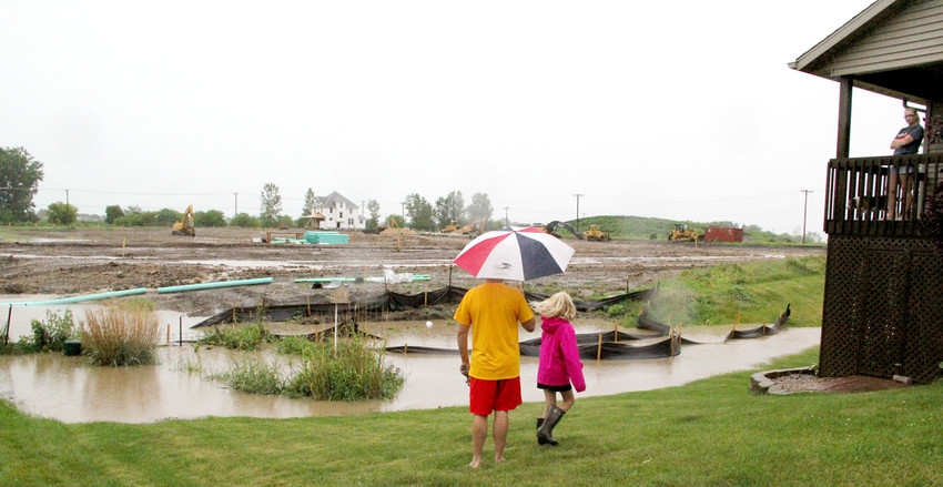ELDRIDGE: Jodie Neiber talks from her deck with neighbors Shannon Budde and his daughter, who came by June 20 to check out rising water off the new Century Villas development next to their Sawgrass Court neighborhood.