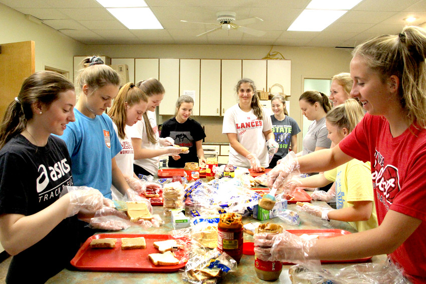 The North Scott High School volleyball team makes sandwiches for the sack lunches.