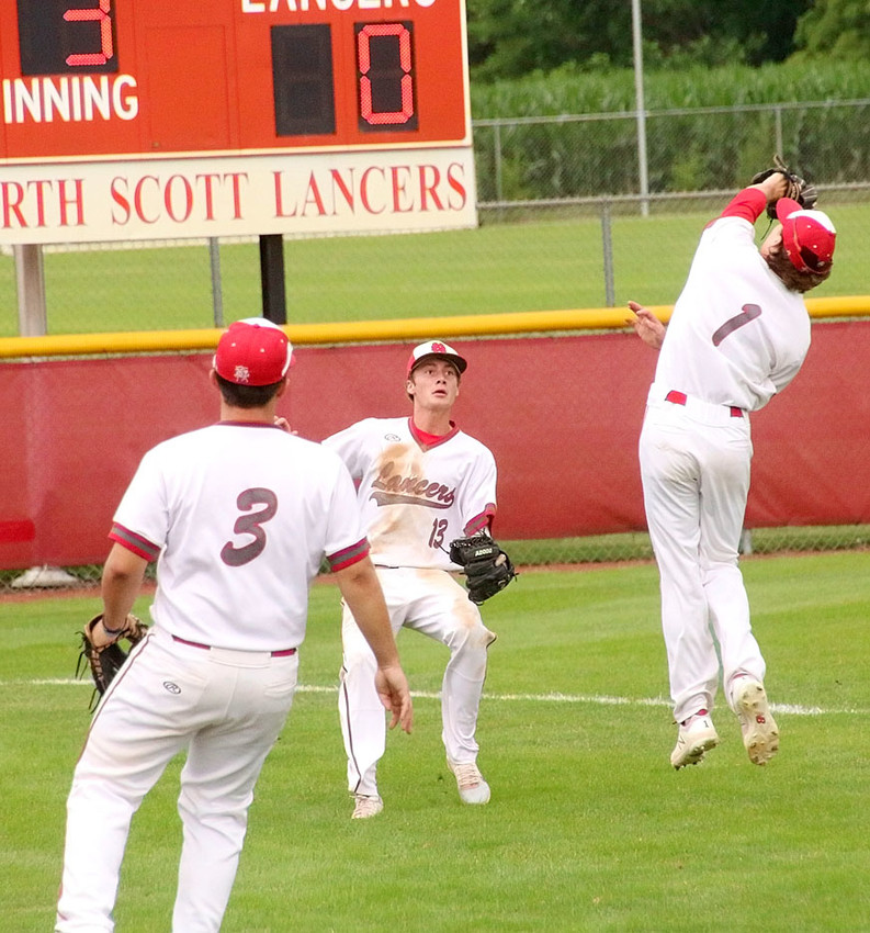 North Scott was the dominant team in Thursday's doubleheader sweep of Davenport Assumption, and the play of the night just might have been this double play in the opener. With leftfielder Austin Helton (13) racing in, Lancer shortstop Cayle Webster (1) roams into foul territory to snap up this ball off the bat of Assumption's Jayce Levy.