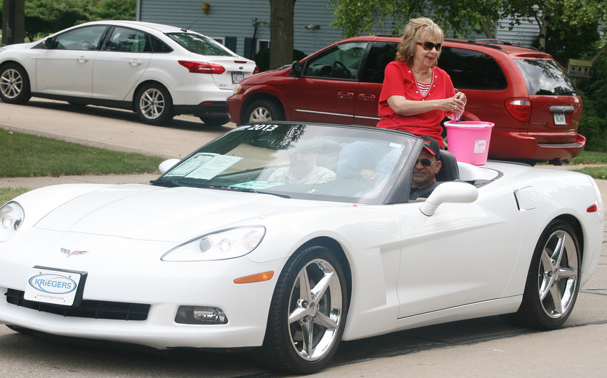 Parade co-grand marshal Fae Harvey throws out some candy. Her husband Norm rode shotgun.