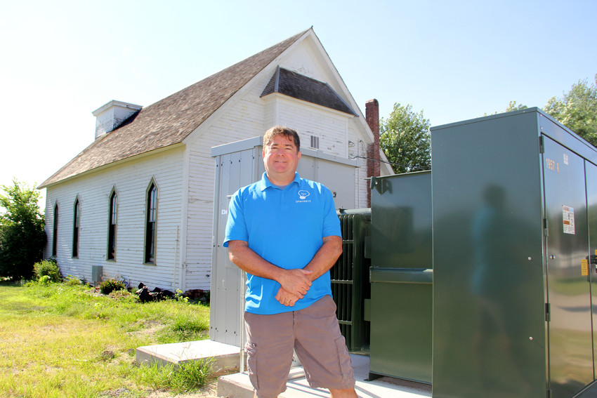 Princeton resident Kevin Stutting, owner of Shared IT, Bettendorf, poses with a 400kw transformer he purchased to power computer servers inside an old church.