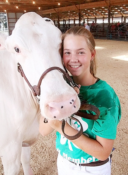 Natalie Knepper poses with her cow during the Dairy show.