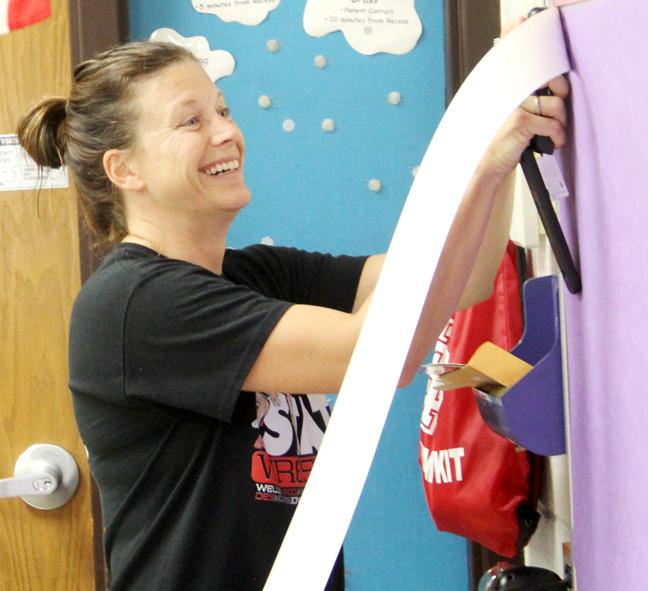 Molly Kelly decorates her Armstrong Elementary classroom.