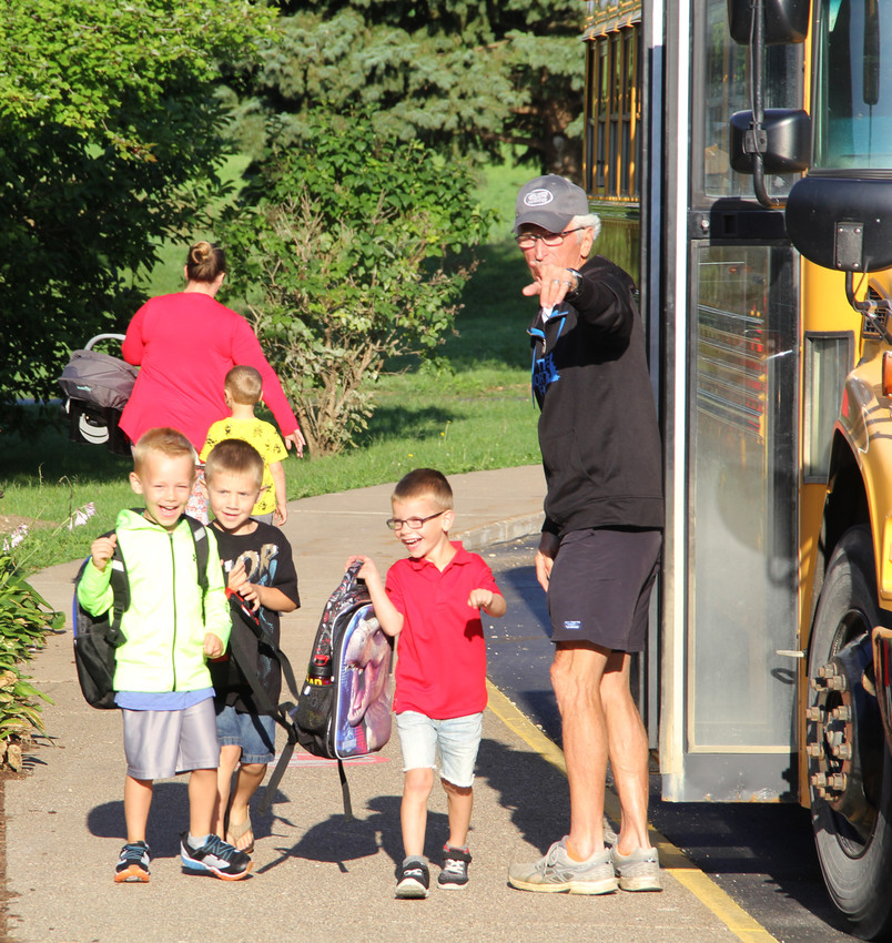 FIRST BUS RIDE: Grissom students bolt from the bus to their first day at school.