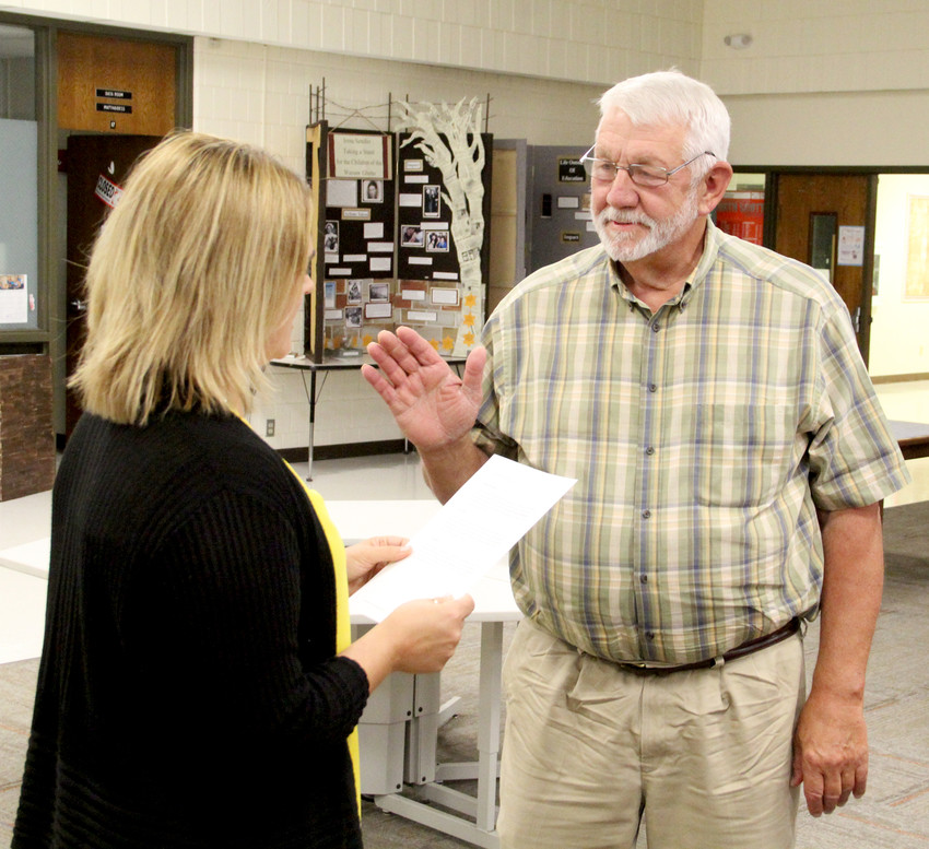 North Scott School Board Secretary Terina Bruns swears in new school board chairman Glen Keppy.