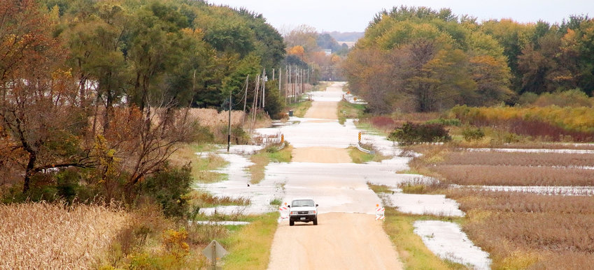 Wapsipinicon River floodwaters creep over 288th Street north of Donahue.  Forecasters expect the river will stay high through this week.