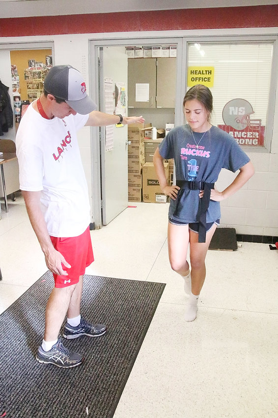North Scott trainer Tim Block watches sophomore volleyball player Kyleigh Westlin test her balance as part of the school's concussion protocol.