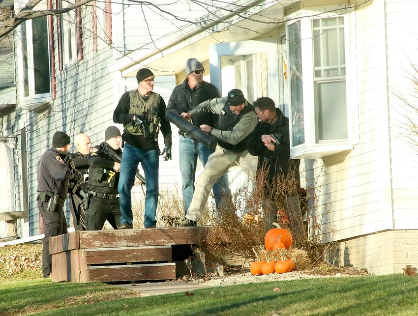 Davenport and Eldridge police join Scott County Sheriff's deputies breaking down a door at 119 N. Eighth St., Eldridge, Nov. 13. Police detained three suspects and arrested a 19-year-old man.