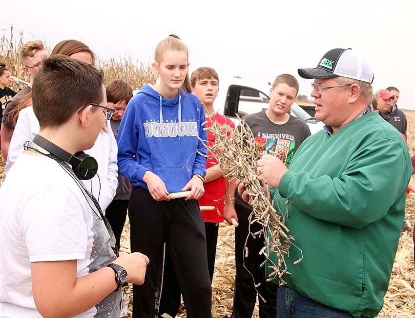 Anna Otte and North Scott Junior High students listen to Jon Lafrenz of P&K Midwest talk about a soybean plant from the school's plot on South First Street.