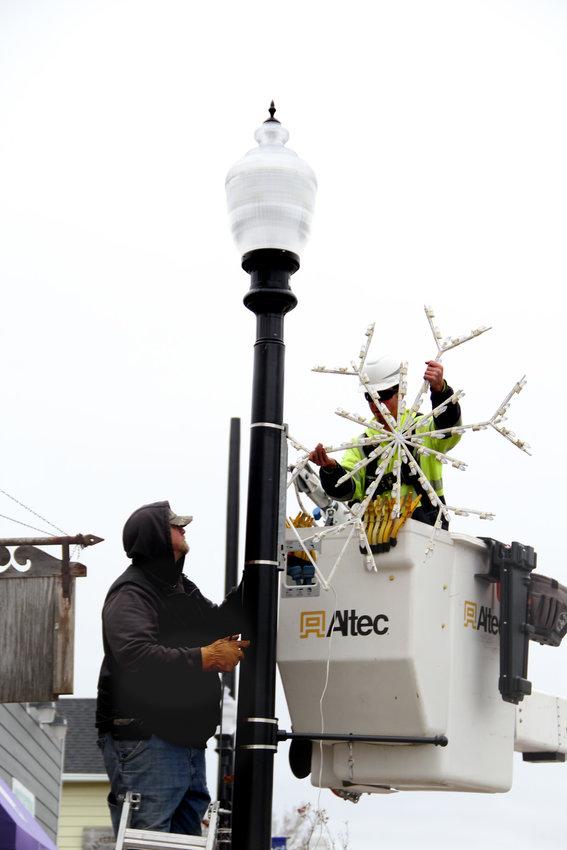 Eldridge utility crews hang a snowflake on 2nd Street in preparation for Friday's Hometown Holidays.
