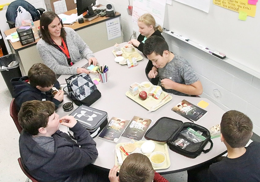 """In between bites of their lunch, Alan Shepard sixth-graders talk with reading teacher Ashley Abdon about the book """"Amulet."""""""