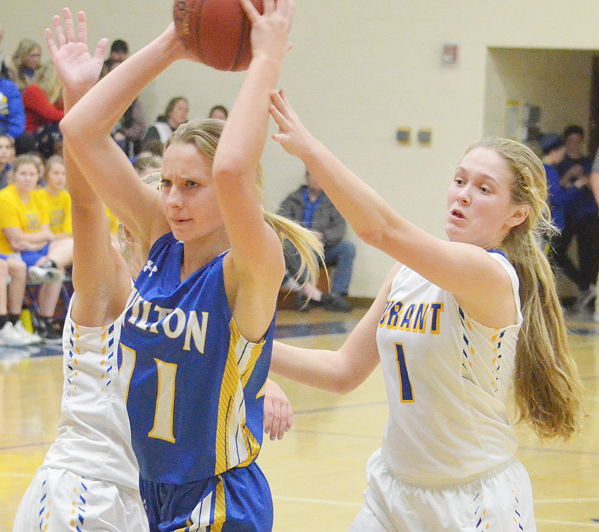 Wilton's Linsey Ford (center) looks to make a pass from the top of the key on the road at Durant Dec. 4 with Hannah Happ (right) guarding. The Beavers earned a Backyard Challenge 79-54 win over the Wildcats.