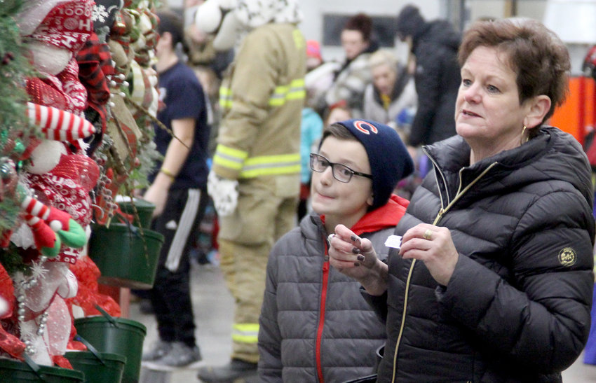 Cindy Arp and grandson Tyson Laughlin, of Eldridge, admire the wreaths on display at the Eldridge Fire Department during Hometown Holidays.