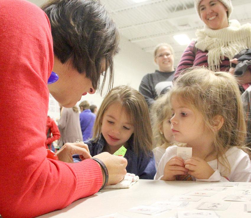 Karee Hodge helps Reegan and Erin Beth Garvin pick their favorite Christmas face decals.
