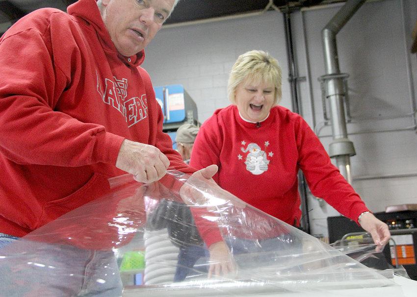 Boise Schoonover and LuAnn Baetke wrap gift baskets.