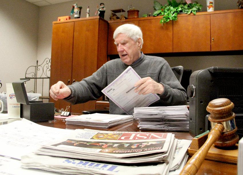 Scott County Treasurer Bill Fennelly reviews vehicle license applications Dec. 20.