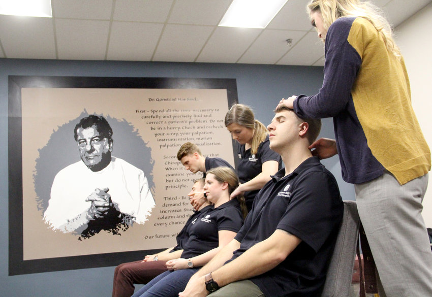 Interns practice techniques at Park View's Lawlor Chiropractic, which continues the Troxell Internship program. The program emphasizes the methods of the late Dr. Clarence Gonstead, pictured in the mural.