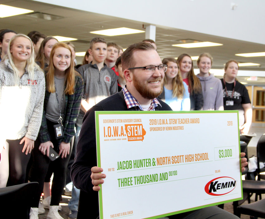 Hunter poses with his FFA and agriculture students and a $3,000 check from Kemin Industries for winning the Iowa Governor's STEM Teacher of the Year Award.
