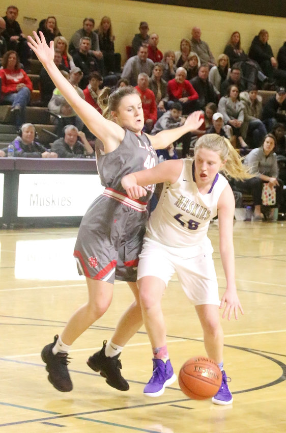 Tough defense and rebounding help has been junior Adriane Latham's calling card in recent games, and here she tries to slow down Muscatine's Madi Petersen.