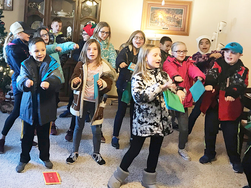 "Third grade students from Kristal Happ's homeroom in Durant visited Hein Manor Dec. 18 to help spread holiday cheer. ""We delivered cards and sang Christmas songs. Hein Manor provided a cookie for each student,"" said Happ. Students are shown above singing and dancing while performing at Hein Manor."