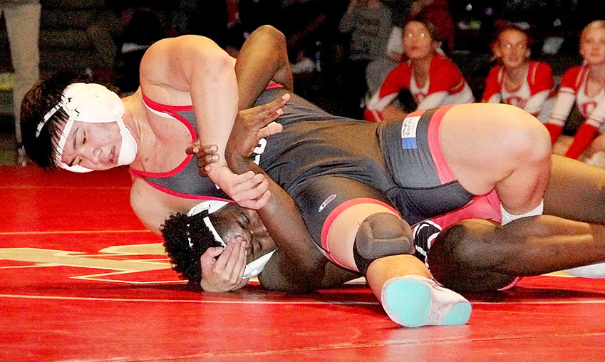 Lancer senior Kevin Diep works hard to score back points against Davenport West's Tyreese Johnson. Unfortunately, Johnson hung on for a 4-3 win.