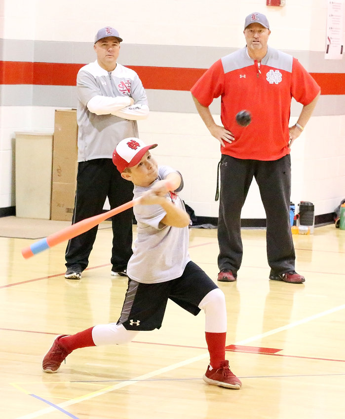 With North Scott baseball coaches Brad Ward and Travis Ralfs looking on, Kolton Engler shows off his power stroke during the 9th annual North Scott Wiffleball Tournament last month.