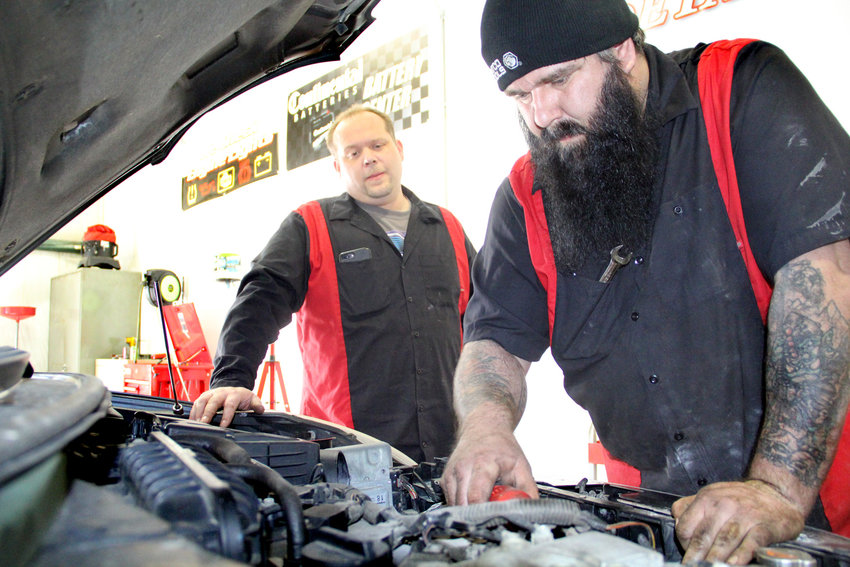 Mike Guldenpfennig and Jay Adkins fix a manifold, their first repair job at Bent River Auto Sales garage at 308 N. 12th Ave., Eldridge.