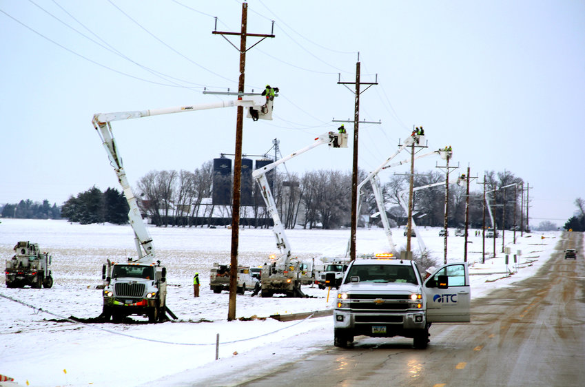 Utility crews restore 14 poles Wednesday knocked down by wind and ice on First Street north of Eldridge.