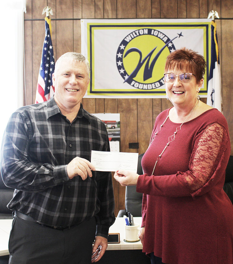 The city of Wilton is a member of the Iowa Association of Municipal Utilities (IAMU) Safety Group Insurance Program. Safety Group members recently earned the largest dividend in the program's history. A check was presented to the city of Wilton on Feb. 14 in the amount of $20,750, which represents a portion of the total 2018 dividend of $5,439,562. The Safety Group dividend is a unique feature of the program, which allows any excess premiums to be returned to members based on the overall results of the program. A portion of the dividend is used by IAMU to support the substantial risk management services extended to members. Wilton City Administrator Chris Ball, left, accepted the check on behalf of the city from Nancy Dunston, right, agency manager and Certified Insurance Counselor at White Pigeon Agency, Inc.