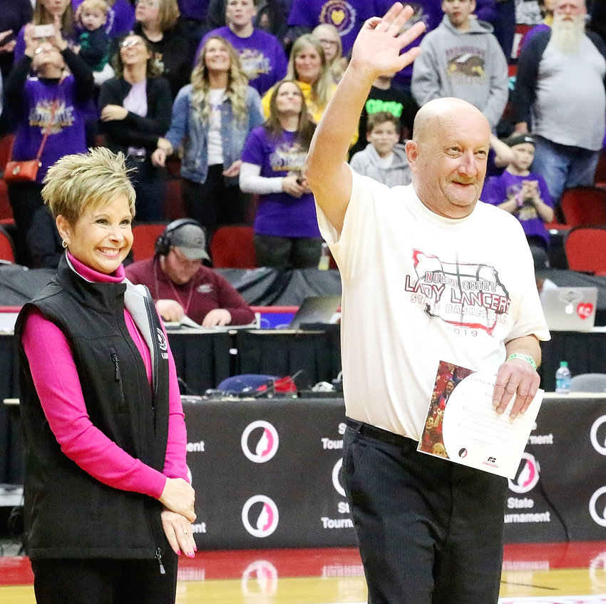 Mike Gesling waves to the crowd after being honored with North Scott's Sportsmanship Award prior to the first-round game. Gesling and his daughter, Kelsey, have attended every home and away game this season.