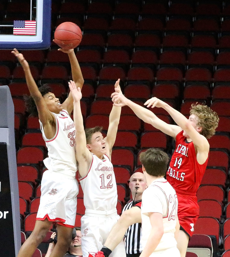 Ty Anderson skies high over teammate Carson Rollinger to block Mason Abbas' shot.