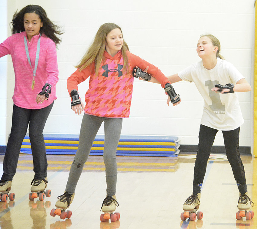 Karley Kelly, Amber Oien and Avery Fitzer laugh while skating in the elementary gym.