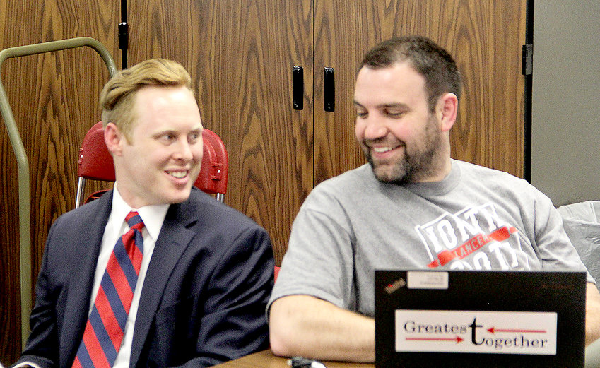 New Grissom principal Kyle Harris and his predecessor, Michael Kline, chat at Monday's school board meeting.