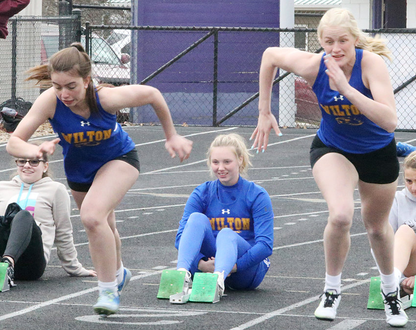 Wilton's Mallory Lange (left) and Payton Ganzer leave the blocks for the 100-meter dash in North Cedar. Ganzer ran to fourth place while Lange finished fifth.