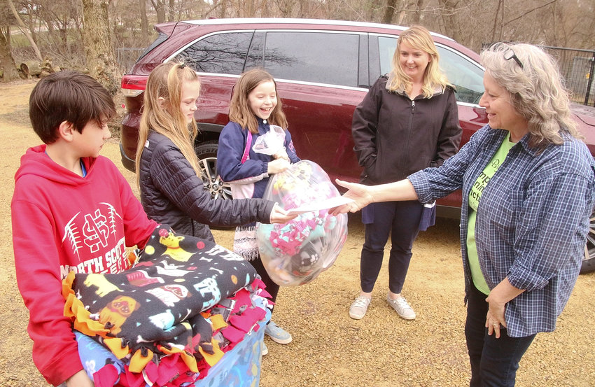 Debbie Wallace, owner of Down By The Creek Companion Animal Sanctuary, is thrilled to receive lap blankets and a monetary donation from fourth-grade students at Alan Shepard Elementary in Long Grove. Pictured are Dylan Kelsey, Maisy Sanders, Katelyn Peck and teacher Angie Clayton.