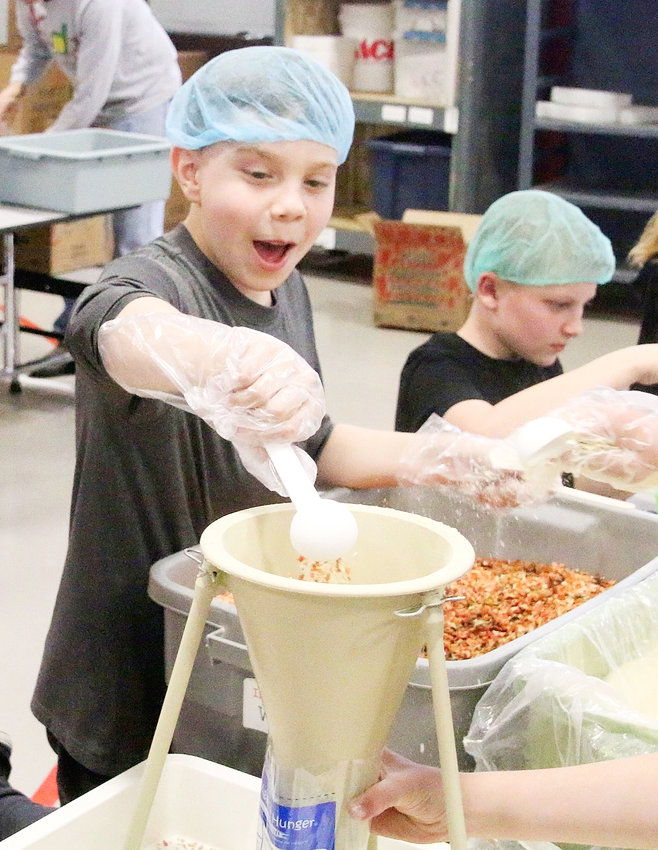 While Henry Rieck (right) appears to be all business, Lucas Hoffman is pretty excited to be making meals for underprivileged individuals.