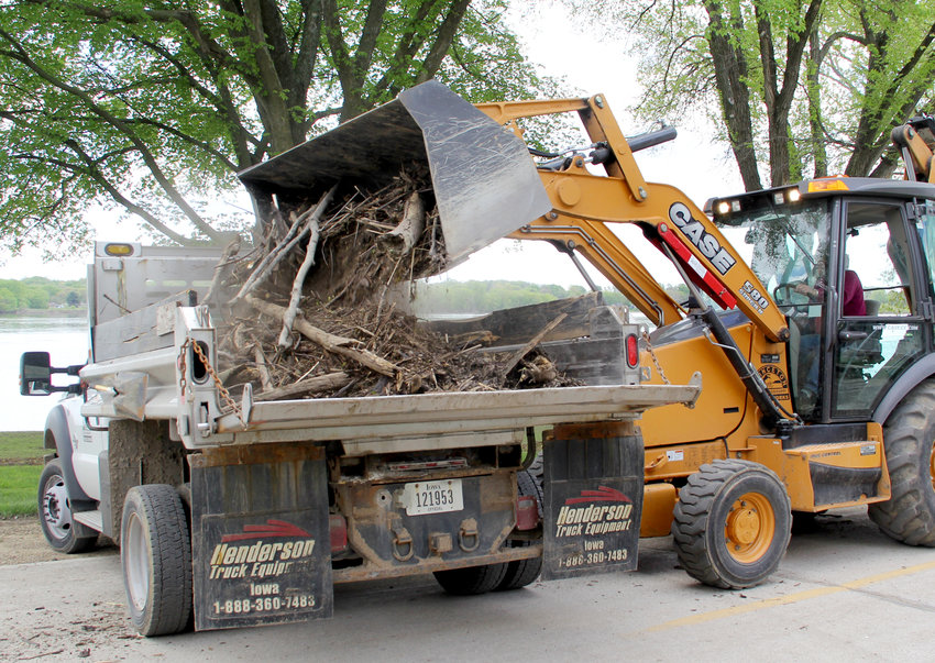 Ty Carstens lifts another load of driftwood off River Drive Monday.