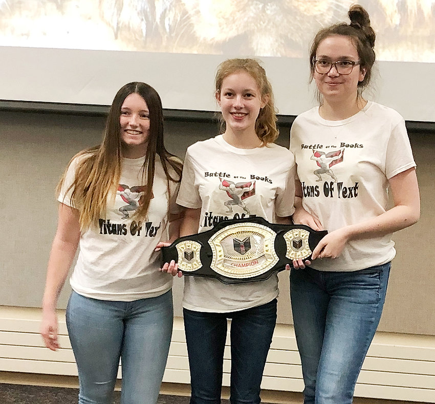 North Scott seniors Abby Kakac, Dana Jamison and Alauna Gentz proudly show off the championship belt after claiming the Battle of the Books championship for the fourth straight year. This year's event was held April 18 at the Bettendorf Public Library.