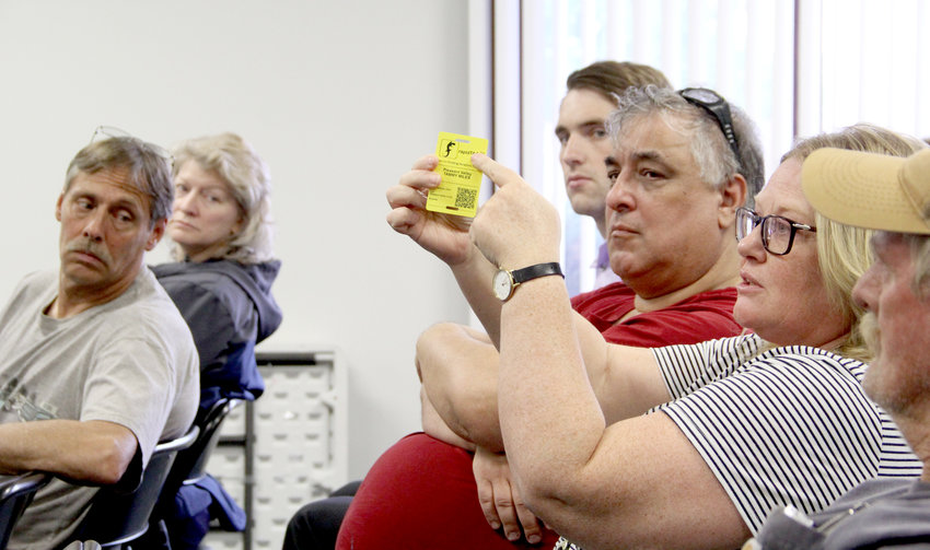 Tammy Miles displays her FEMA card at the May 22 Scott County flood town hall at the LeClaire Fire station. Miles obtained the card at the flood center established at North Park Mall.