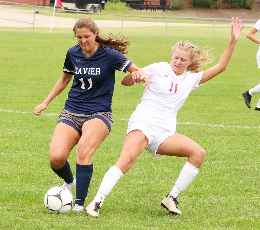 NS senior Kaitlyn Ruwe battles Xavier's Quinn Hanigan for a loose ball.
