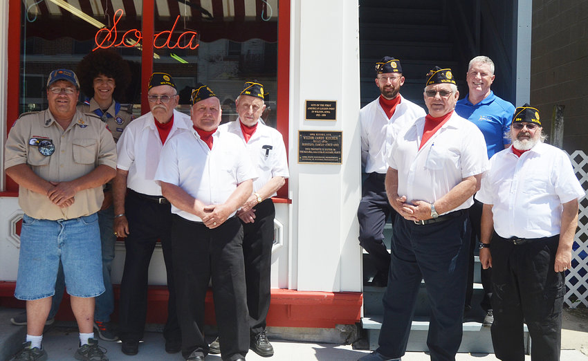 Wilton Boy Scout and Legion members in attendance at the dedication and 100th birthday event June 8 gathered around the new plaque posted by the stairwell to the first ever Wilton Legion Post 584 meetings above the Candy Kitchen. Pictured from left include Rod Ochiltree, Marshall Ochiltree, George Leggins, Roger Bender, Ken Connover, Greg Shuger, Gordon Arnold, Chris Ball and Kevin Wright.