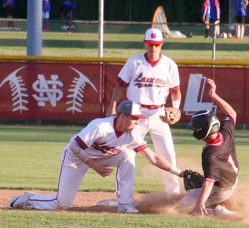 After a perfect throw from catcher Griffin Wilder, Lancer shortstop Austin Schneider puts the tag on Linn-Mar's Andy Althoff to thwart this stolen base attempt.