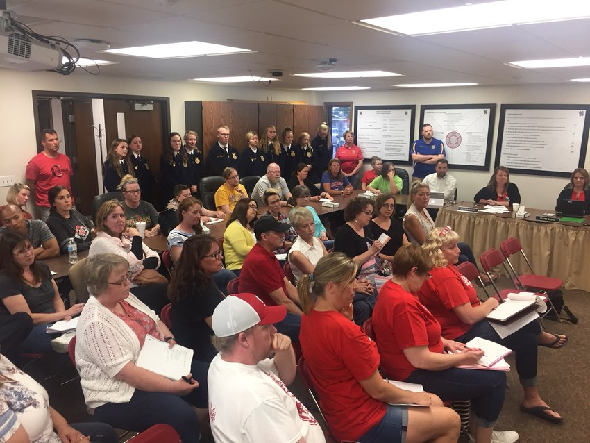 More than 50 North Scott teachers, aides and staff crowded the school board meeting room Monday to share fears about imminent health insurance cost increases.