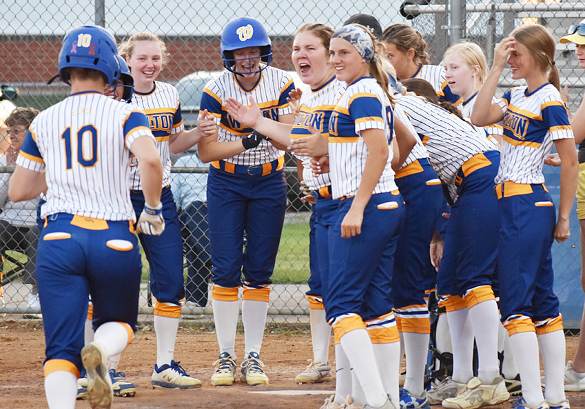 Wilton's Chloe Wells (left No. 10) is shown approaching happy teammates at home plate after a pinch-hit home run in what would be the final at-bat of her season June 20 in a home win over Cascade. Wells broke a bone in her hand and recently had surgery, ending her sophomore season.